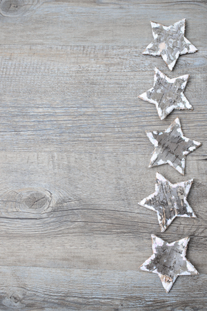 old backgrounds: Christmas decoration from birch bark stars over the wooden background Stock Photo