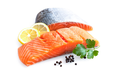 fresh salmon fillet with parsley and lemon slices isolated on white