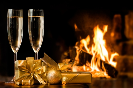 two glasses and gift boxes  in front of fireplace photo