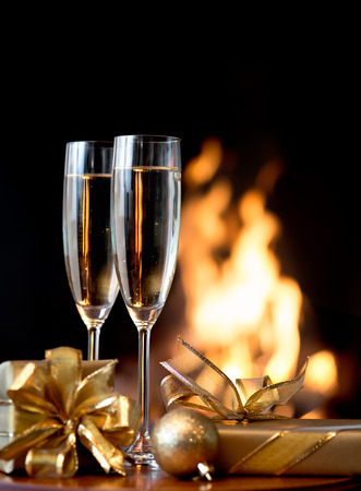 Two champagne glasses and gift boxes  in front of fireplace photo