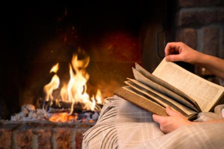handen van de vrouw leesboek door open haard Stockfoto