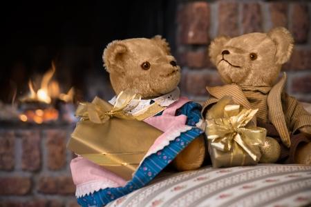 vintage teddy bears: Coppia d'epoca orsacchiotti con regali di Natale davanti al camino Archivio Fotografico