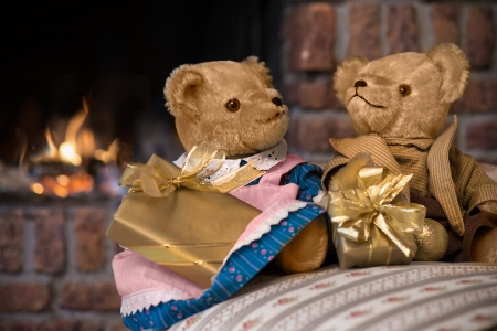 Couple vintage teddy bears with christmas gifts in front of fireplace photo