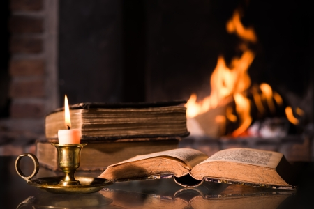 An open Bible with a burning candle in front of fireplace