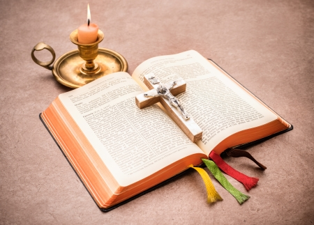 A bible open on a table with  burning candle