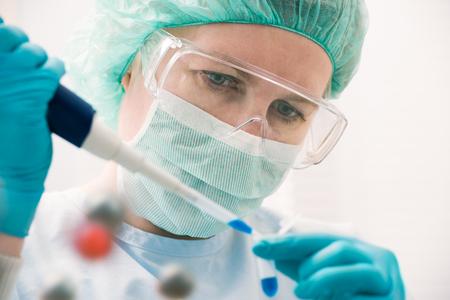 Científico con cuentagotas a trabajar en el laboratorio