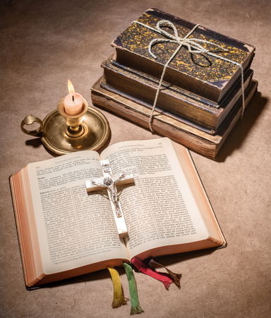 A bible open on a table with  burning candle photo