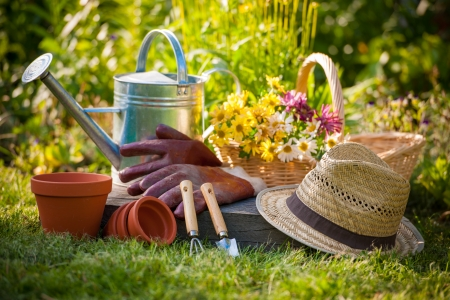 home garden: Gardening tools and a straw hat on the grass in the garden Stock Photo