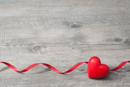 Corazón con la cinta roja en la madera vieja, Día de San Valentín