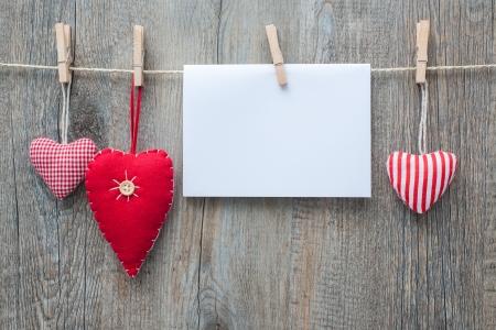 Boodschap en rode harten op de waslijn tegen houten Stockfoto
