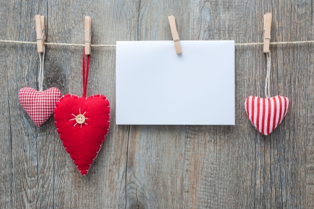 Message and red hearts on the clothesline against wooden  photo