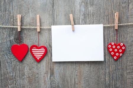 corazones de amor: Mensaje y corazones rojos en la ropa contra madera