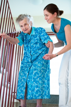 alzheimer: Senior woman is climbing stairs with home caregiver Stock Photo