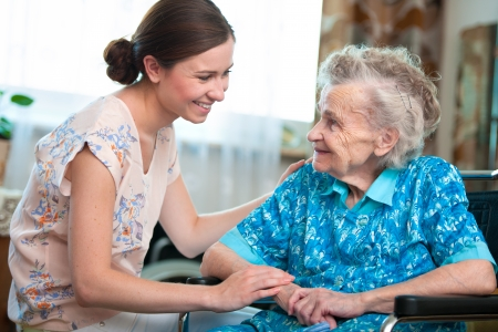 anciano feliz: Mujer mayor con su cuidador en el hogar