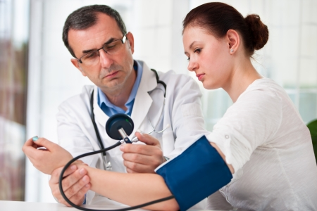 Male doctor checking young woman blood pressure photo
