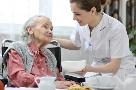 haushaltshilfe: Senior Frau isst am Altenheim Mittagessen
