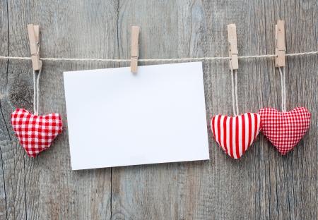 Boodschap en rode harten op de waslijn tegen houten achtergrond Stockfoto