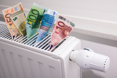 costly: heating thermostat with money, expensive heating costs concept Stock Photo