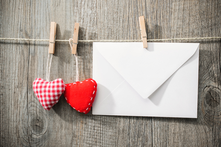 Message and red hearts on the clothesline against wooden background photo