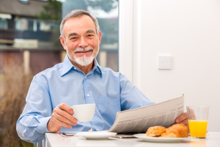 Happy senior man at breakfast with newspaper Stock Photo - 25150784
