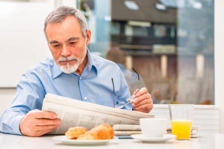 Senior man with glasses reading newspaper at breakfast Stock Photo - 25150785
