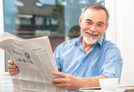 Happy senior man at breakfast with newspaper Stock Photo - 25150786