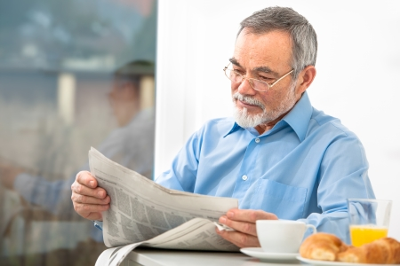 Senior man with glasses reading newspaper at breakfast photo