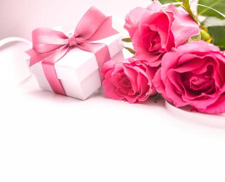 バラの花束と白い背景の上のギフト ボックス