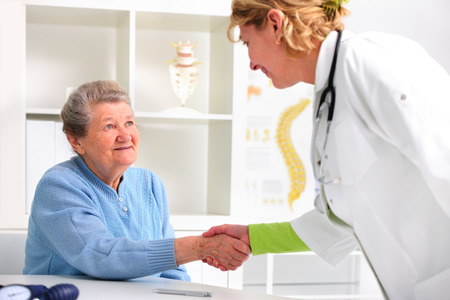 Doctor shakes hands with a female senior patient photo