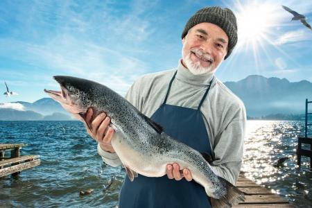 フィッシャー、漁港でアトランティック サーモンの大きな魚を保持
