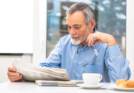 Happy senior man at breakfast with newspaper photo