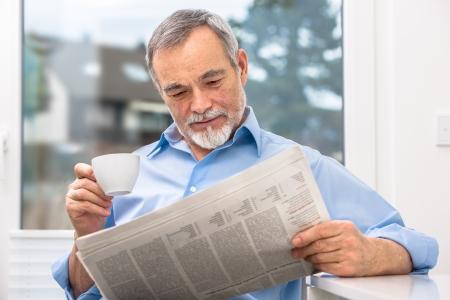 oude krant: Gelukkig senior man bij ontbijt met krant