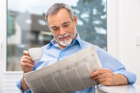 Happy senior man at breakfast with newspaper Stock Photo - 25273874