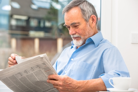 Happy senior man at breakfast with newspaper Stock Photo