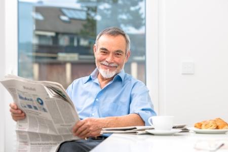 Happy senior man at breakfast with newspaper Stock Photo - 25273854