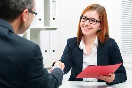 entrevista de trabajo: El hombre y la mujer apret�n de manos para sellar un acuerdo tras una reuni�n de reclutamiento laboral