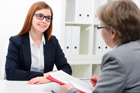interview job: Mujer joven discutiendo durante una entrevista de trabajo en la oficina Foto de archivo