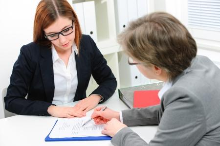 entrevista de trabajo: Mujer joven discutiendo durante una entrevista de trabajo en la oficina Foto de archivo