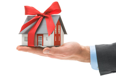 hand holding house: Real estate agent holds architectural model with red bow