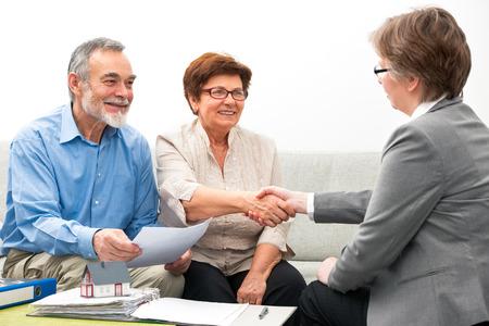 Senioren ouple ontmoeting met financieel adviseur, handdruk