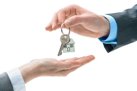 renter: Man is handing a house key to other hands. Concept of real estate and deal Stock Photo