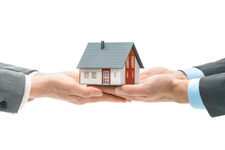 Hands giving house model to other hands. Concept of real estate and deal photo