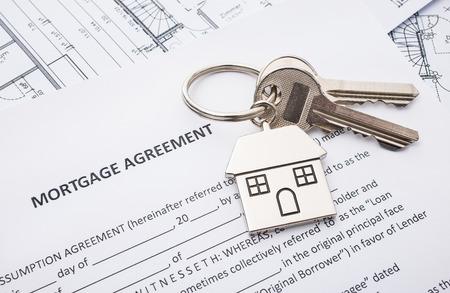 家の形をしたキーリングと住宅ローン契約の適用 写真素材