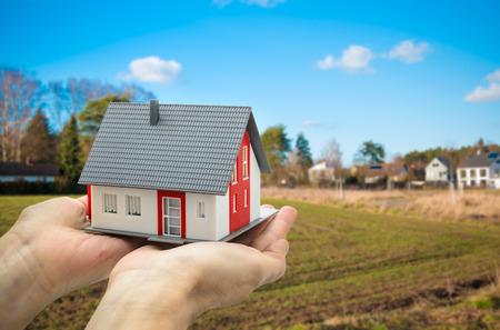 Handen die een huis model tegen bouwgrond Stockfoto