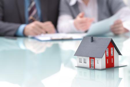 Zakenman tekent contract achter huis architectonisch model