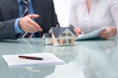 n�gocier: Discussion avec un agent immobilier au bureau Banque d'images