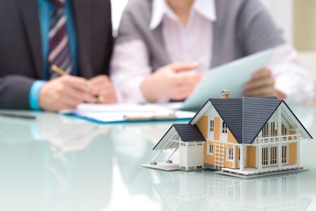 Firma un contrato Hombre de negocios detrás de la casa modelo arquitectónico Foto de archivo