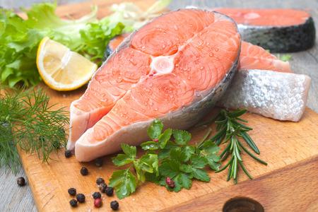 omega 3: Raw salmon fish steaks with fresh herbs on cutting board