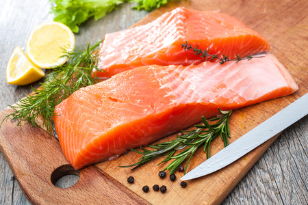 Raw salmon fish fillet with fresh herbs on cutting board Reklamní fotografie