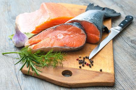 Raw salmon fish steaks with fresh herbs on cutting board photo